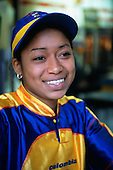 San Jose, Costa Rica. Smiling girl shop assistant in bright yellow and blue uniform.