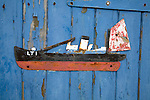 Old scrap metal model of ship on blue painted shed wall, Felixstowe Ferry, Suffolk, England