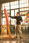 An artist paints in a college studio.
