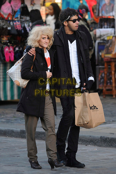 KATIE WAISSEL & FRIEND .X Factor's Katie Waissel seen shopping with a friend in Covent Garden, London, England, UK, November 10th 2010..full length  bench carrier bag black duffel duffle coat green khaki trousers blue navy bag arm around walking I heart 80's top white .CAP/IA.©Ian Allis/Capital Pictures.