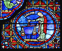 A woman dressed as Virgo in green dress and red cloak, uses scales to balance, perhaps finding an equilibrium between day and night in this time of winter solstice, section of Libra from the Zodiac and the labours of the months stained glass window, 1217, in the ambulatory of Chartres Cathedral, Eure-et-Loir, France. This calendar window contains scenes showing the zodiacal symbol with its corresponding monthly activity. Chartres cathedral was built 1194-1250 and is a fine example of Gothic architecture. Most of its windows date from 1205-40 although a few earlier 12th century examples are also intact. It was declared a UNESCO World Heritage Site in 1979. Picture by Manuel Cohen