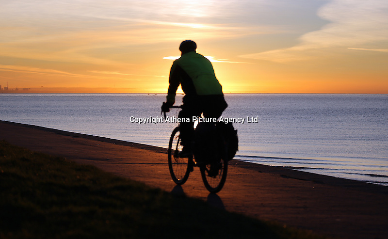WEATHER PICTURE WALES<br /> Pictured: A cyclist rides along the sea front as the sun rises over Swansea Bay in Wales, UK. Wednesday 30 November 2016<br /> Re: Low temperatures with sunshine in most parts of the UK