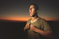 "SF.Marines.#43.db.08-22... Marine recruit Gilbert Escobedo stands yells in his underwear before bedtime, screaming the chant of ""Ready to fight, ready to kill, ready to die, but never will."" Recruits were forced to scream this chant at the top of their lungs before being allowed to climb into their bivouac for the night to sleep. On this night and all of the third of four weeks of training at Camp Pendleton during this second phase, recruits slept outside....Photo by David Bohrer/FTT."