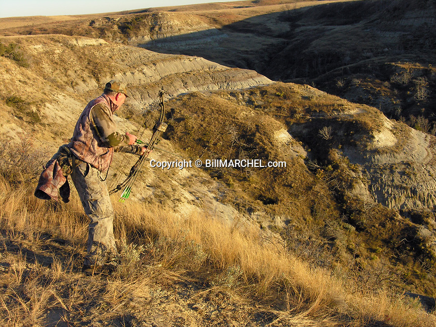 00105-040.10 Bowhunting (DIGITAL) A well-camouflage archer peers over ridge while hunting in the Badlands.  Mule Deer, prairie.  H3R1