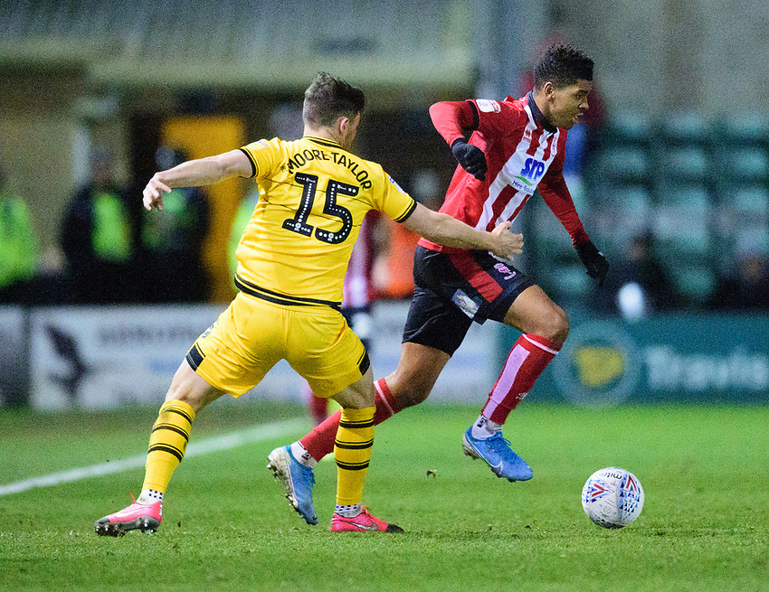 Lincoln City's Tyreece John-Jules vies for possession with  Milton Keynes Dons' Jordan Moore-Taylor<br /> <br /> Photographer Andrew Vaughan/CameraSport<br /> <br /> The EFL Sky Bet League One - Lincoln City v Milton Keynes Dons - Tuesday 11th February 2020 - LNER Stadium - Lincoln<br /> <br /> World Copyright © 2020 CameraSport. All rights reserved. 43 Linden Ave. Countesthorpe. Leicester. England. LE8 5PG - Tel: +44 (0) 116 277 4147 - admin@camerasport.com - www.camerasport.com