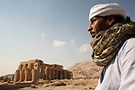 An Egyptian man in traditonal dress with The Ramesseum Temple in the backgound. Luxor. Egypt
