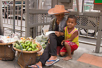Woman and child selling fruit on Bangkok street.