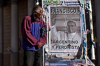 """A man walks next to a poster of Pope Francis than reads in spanish """"Argentinean and Peronist"""" in a street in Buenos Aires March 17, 2013. Photo by Juan Gabriel Lopera / VIEWpress."""