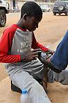 ANGOLA Waku Kungo, child labour, boy polish shoes / ANGOLA Waku Kungo, Kinderarbeit, Junge putzt Schuhe zum Geld verdienen