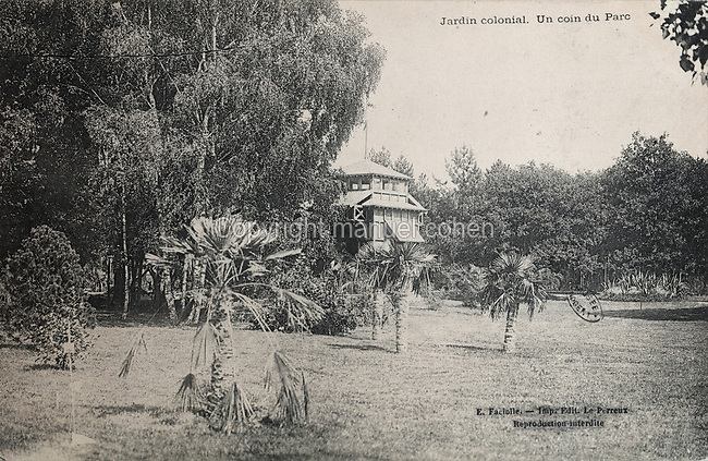 Gardens with palm trees and the Pavillon de la Reunion or Pavillon de la Martinique in the distance, in the Jardin d'Agronomie Tropicale, or Garden of Tropical Agronomy, in the Bois de Vincennes in the 12th arrondissement of Paris, postcard from the nearby Musee de Nogent sur Marne, France. The garden was first established in 1899 to conduct agronomical experiments on plants of French colonies. In 1907 it was the site of the Colonial Exhibition and many pavilions were built or relocated here. The garden has since become neglected and many structures overgrown, damaged or destroyed, with most of the tropical vegetation disappeared. The site is listed as a historic monument. Picture by Manuel Cohen / Musee de Nogent sur Marne