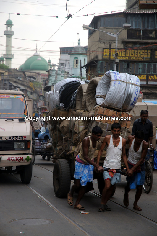 Indian porters pull a heavily loaded cart in Kolkata. Indian porters generally earns about 2 usd a day. In this developing country a section of the society became rich but most of its population still lives under the povery line. Kolkata, West Bengal, India. ARINDAM MUKHERJEE