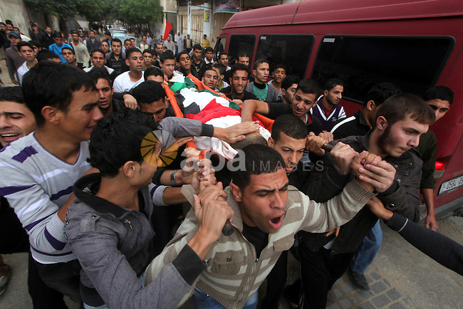 Mourners carry the body of killed Palestinian civilian Ahmad Dardasawy, 18, during his funeral in Gaza City on November 11, 2012 , the day after he was killed in Israeli shelling as clashes erupted along the Isreali-Gaza Strip border. The flare-up was one of the most serious since Israel's devastating 22-day operation in the Gaza Strip over New Year 2009. Photo by Ashraf Amra