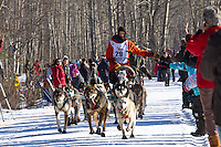 Nick Petit and team run past spectators on the bike/ski trail during the Anchorage ceremonial start during the 2014 Iditarod race.<br /> Photo by Britt Coon/IditarodPhotos.com