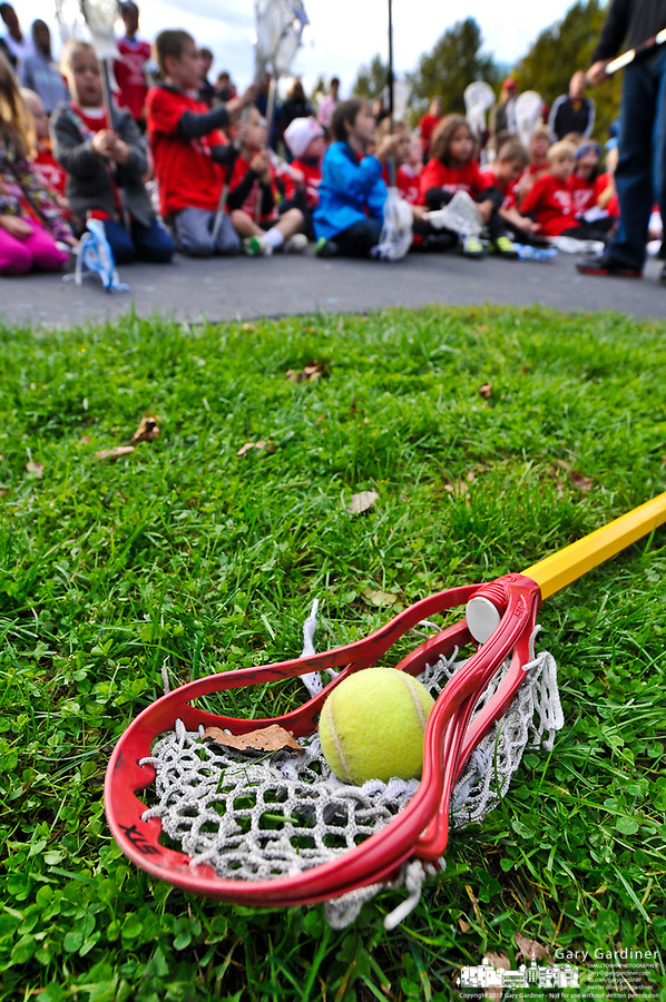 A tennis ball sits in a lacrosse stick as young athletes listen to coaches before a lacrosse clinic and practice at a city park in Westerville, OH.