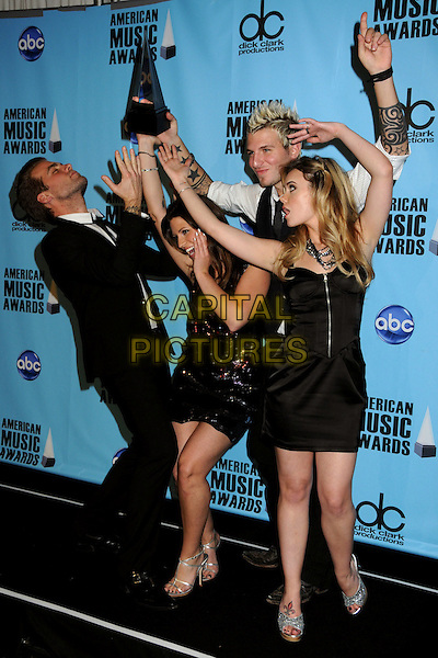 GLORIANA - Tom Gossin, Cheyenne Kimball, Mike Gossin and Rachel Reinert .At the 2009 American Music Awards - Press Room held at the Nokia Theatre L.A. Live, Los Angeles, California, USA, .22nd November 2009..AMA AMAs full length band group black waistcoat tie suit white shirt strapless sequined sequin dress hands arms raised up silver sandals strappy tattoos trophy award .CAP/ADM/BP.©Byron Purvis/AdMedia/Capital Pictures.
