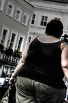 An obese woman walking along a street in a town