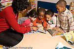Education preschool 4 year olds female teacher working with group of children 3 boys and 1 girl looking at book and talking horizontal