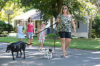 Lori Clappier of Lala's Leash walks her dogs Lily (left) and Jojo (right) Thursday August 13, 2015 in New Britain, Pennsylvania. Neighbors walk behind them. (Photo by William Thomas Cain)