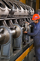 Worker testing train motor at locomotive repair factory