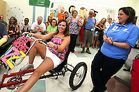 Elizabeth is applauded while entering her sendoff party on a tricycle  Friday at On With Life, a brain injury rehabilitation center.