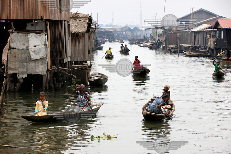 People paddle their canoes through the Makoko district that is on Lagos Lagoon.