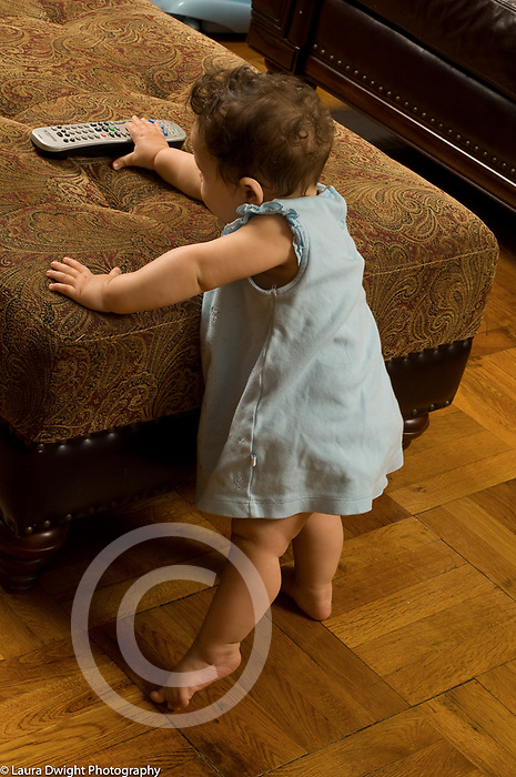 9 month old baby girl standing with support reaching for TV remote on hassock
