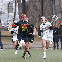 Boston College midfielder Kate McCarthy (20) brings the ball forward as University of Maryland midfielder Beth Glaros (20) defends..University of Maryland (black) defeated Boston College (white), 13-5, on the Newton Campus Lacrosse Field at Boston College, on March 16, 2013.