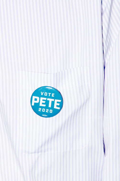 "A man wears a button reading ""Vote Pete 2020"" after Democratic presidential candidate and South Bend mayor Pete Buttigieg spoke at a house party with the Bedford Democrats in Bedford, New Hampshire, on Sat., Apr. 20, 2019. The candidate stood on a chair throughout his speech."