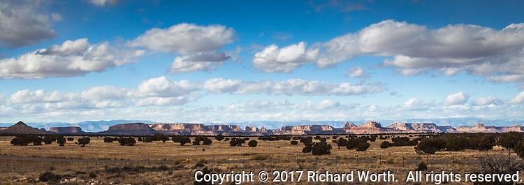 High plateaus in Utah under blue cloud filled skies.