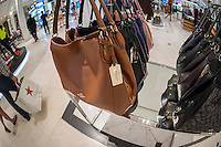 Coach handbags on display at the Coach boutique within Macy's in New York on Tuesday, August 4, 2015. Coach global sales dropped 12% last quarter but still beat analysts' expectations. Coach is in the process of turning around the company, dropping discounting, promotions and cutting back on expansion. They are also diversifying their product line after purchasing Stuart Weitzman shoes.  (© Richard B. Levine)