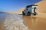 Africa, Mauritania, Sahara Desert, nr. Nouakchott. Land Rover Defender TD5 Station Wagon driving on the beach along the coastal piste from Nouakchott to Nouadhibou through the nature reserve Parc National du Banc D'Arguin in Mauritania. --- RELEASES AVAILABLE! Automotive trademarks are the property of the trademark holder, authorization may be needed for some uses.