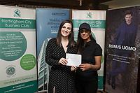Denada Berisha of Remus Uomo gives a raffle prize to Karen Sandhu