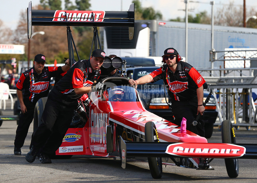 Feb 7, 2014; Pomona, CA, USA; Crew members push NHRA top fuel dragster driver Leah Pritchett from the staging lanes out onto the track during qualifying for the Winternationals at Auto Club Raceway at Pomona. Mandatory Credit: Mark J. Rebilas-
