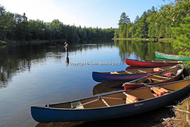 Canoes and a man fishing at a campsite along the St. Croix River, Washington County, Maine, USA
