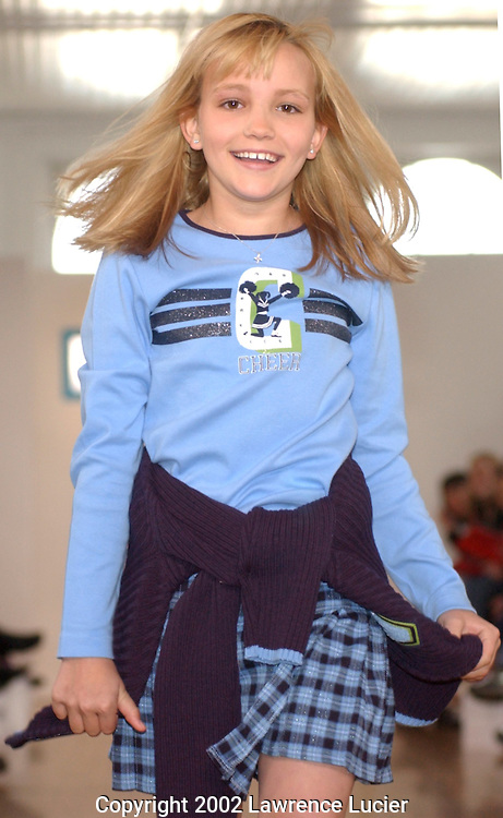 Model Jamie Lynn Spears finishes a cartwheel while wearing a blue long sleeve graphic cheerleader tee with a blue plaid skirt and blue zip-front sweater  April 11, 2002, in New York. This item is part of the Fall 2002 Kids R Us fashion collection..