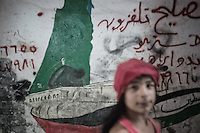 In the street of Shatila the Palestinian's flag is paint on the walls with symbolic writing and drawings. Here the boat to Palestine to represent the come back. Beirut. Lebanon. August 2015