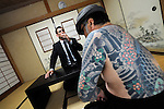 "Jake Adelstein, a former reporter at Japan's largest daily newspaper, Yomiuri Shimbun, and author of ""Tokyo Vice"", speaks with his bodyguard, a former yakuza mobster who goes by the name ""Mochizuki,"" at an undisclosed location in Japan on Aug. 29, 2008. In 2005 American Adelstein uncovered a scandal involving senior members of Japan's mafia, the yakuza, visiting a medical center in Los Angeles to undergo liver transplants, despite being bared from entry due to having criminal records or suspected affiliation with Japanese organized crime groups. Within days, however, Adelstein was visited by mob members and told to either ""erase the story or be erased."" He took the former option and resigned from the Yomiuri, though a leak of his story at the time of this interview pushed Adelstein and his family into hiding..Photographer: Robert Gilhooly"