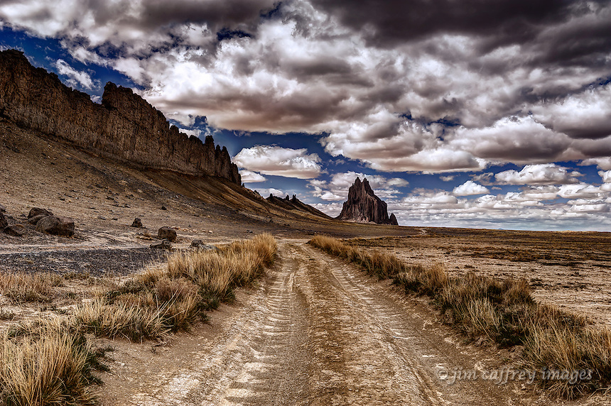 A dirt road along the Shiprock lava dike with Shiprock in the distance