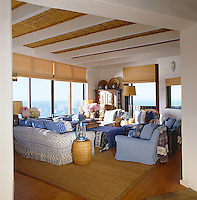The living room is decorated with a mixture of blue and white textiles and has a spectacular view of the Indian Ocean