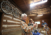 NWA Democrat-Gazette/DAVID GOTTSCHALK   Caye Mott (from left) uses a niddy noddy to wrap yarn Wednesday, May 3, 2017, during a a Spin-A-Round meeting of the Wool and Wheel Handspinners with Harrison McNeill, Kristy Casamayor and Kathleen McGill in the Latta Barn at Prairie Grove Battlefield State Park. The group meets every first Wednesday of the month at the park and every third Saturday at Ozark Folkways in Winslow. The group is open to the public and invites participation and observation.
