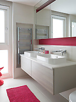 Small touches of bold, pinky red colour liven up an otherwise neutral bathroom.