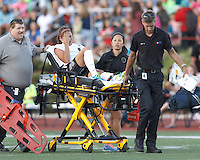 Injured Portland Thorns FC forward Alex Morgan (13) is removed from the field. In a National Women's Soccer League (NWSL) match, Boston Breakers (blue) defeated Portland Thorns FC (white/black), 2-1, at Dilboy Stadium on August 7, 2013.