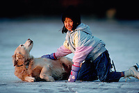 Young Asian-American girl wearing ice skates playing with her golden retriever on the ice.