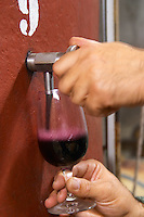 Domaine Entretan, J-C and D Plantade in Roubia. Minervois. Languedoc. Pouring a wine sample in a glass. Painted steel vats. Concrete fermentation and storage vats. Tank spout. Owner winemaker. France. Europe.