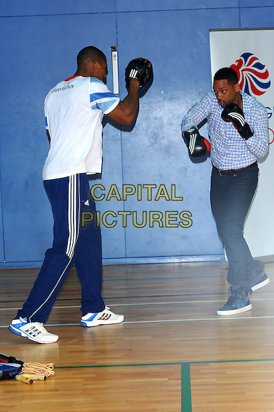 Anthony Joshua & Will Smith .Will Smith meets British Olympic hopefuls at  Ethos Sports Centre, Imperial College, London, England..May 16th, 2012.full length t-shirt white blue jeans denim black white check shirt boxing gloves sport gesture sport.CAP/CJ.©Chris Joseph/Capital Pictures.