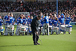 "Portsmouth 1 Southampton 1, 18/12/2012. Fratton Park, Championship. A groundsman making preparations to the pitch in front of a samba band dressed in Portsmouth colours at Fratton Park stadium before their club take on local rivals Southampton in a Championship fixture. Around 3000 away fans were taken directly to the game in a fleet of buses in a police operation known as the ""coach bubble"" to avoid the possibility of disorder between rival fans. The match ended in a one-all draw watched by a near capacity crowd of 19,879. Photo by Colin McPherson."