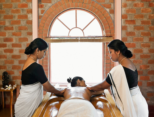 Woman Receiving Abhyanga, Ayurvedic Massage, Kairali Ayurvedic Health Resort, Palakkad, Kerala, India. Abhyanga is an Ayurvedic oil massage that involves covering the client in oil, and massaging him or her using long rhythmic strokes. Traditionally two therapists perform the massage in synchronized motions.
