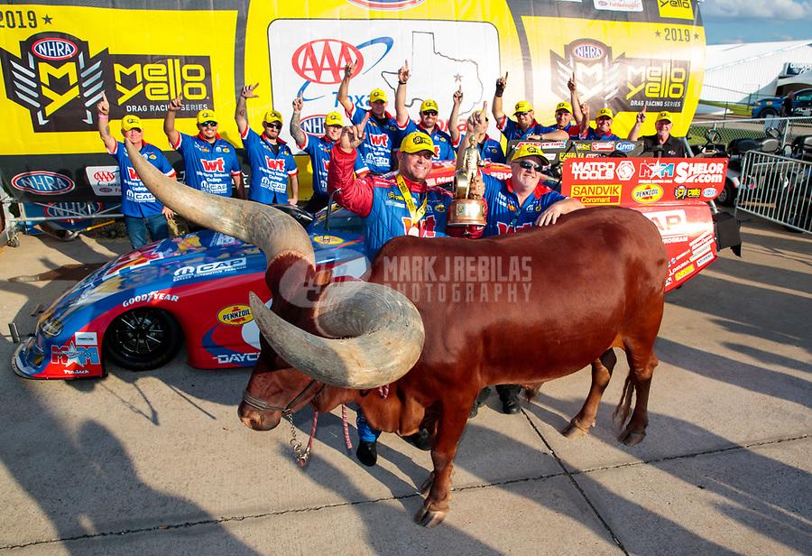 Oct 20, 2019; Ennis, TX, USA; NHRA funny car driver Matt Hagan and crew celebrate alongside a live bull after winning the Fall Nationals at the Texas Motorplex. Mandatory Credit: Mark J. Rebilas-USA TODAY Sports