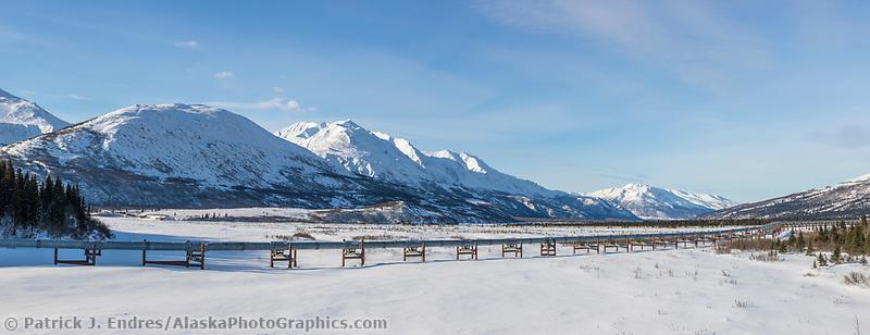 Trans Alaska oil pipeline traverses miller creek in the snow covered Alaska Range mountains.