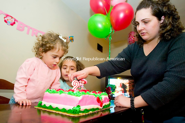 WATERTOWN, CT- 29 DEC 06- 123006JT33- <br /> Alesia Faith Pandiscia and her sister Olivia, 5, watch as their mother Carmela lights the candle on Alesia's birthday cake at the Pandiscia's Watertown home on Dec. 29, 2006.<br /> Josalee Thrift Republican-American